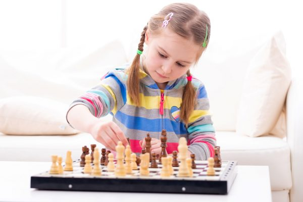 Cute little girl playing chess at home