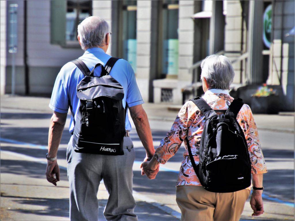 Odwrócona plecami para trzyma się za ręce i idzie po ulicy.