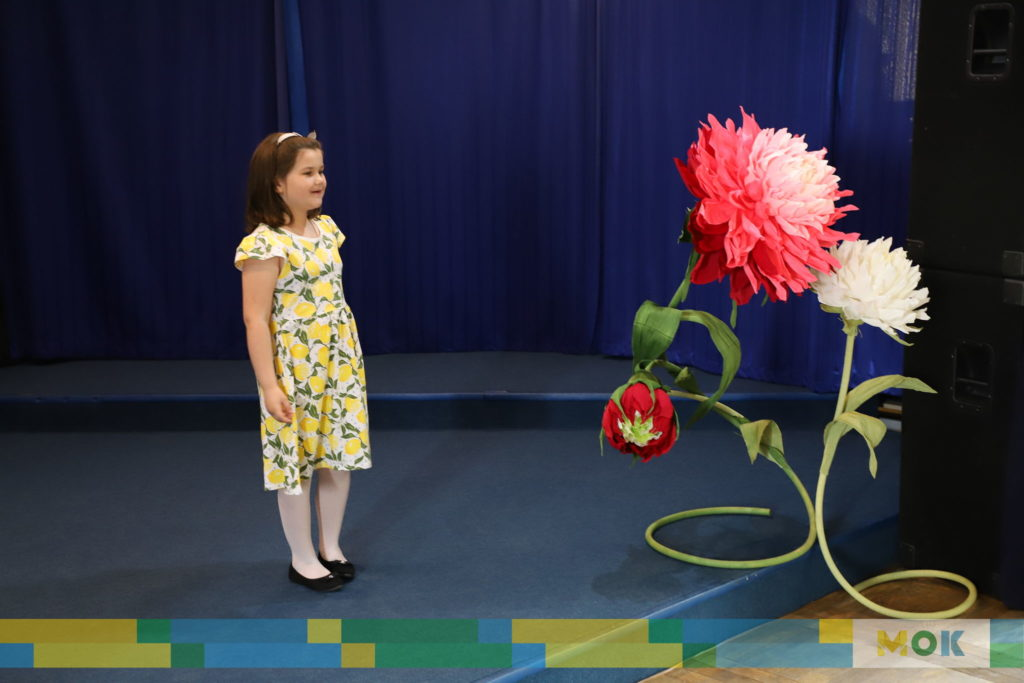 Dziecko recytuje wiersz na scenie.