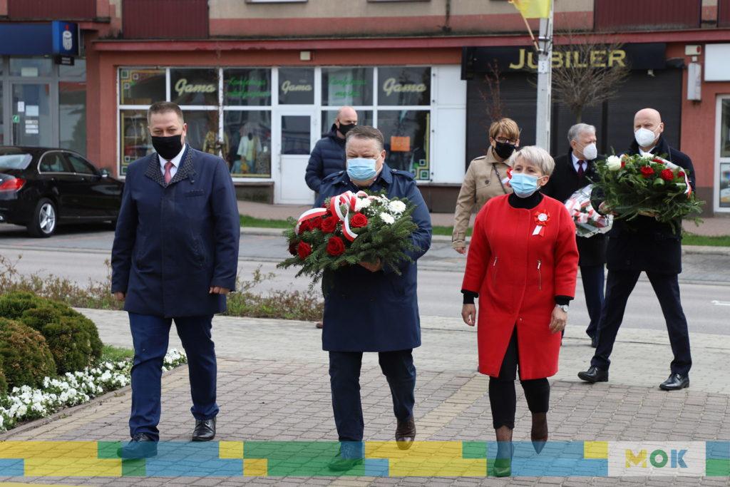Grupa ludzi składająca kwiaty pod pomnikiem pamięci.