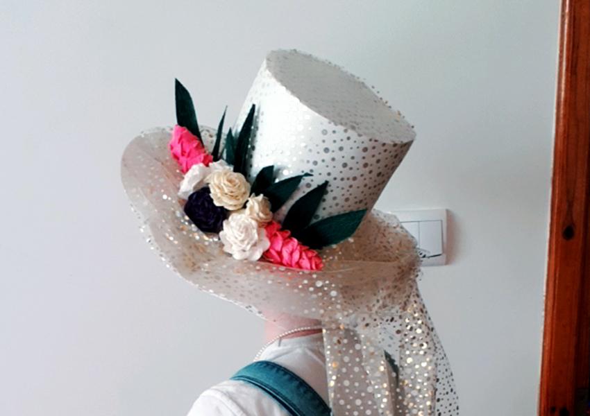 Biały kapelusz z dodatkiem kwiatowej kompozycji.
