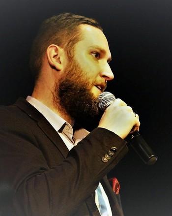 Zdjęcie przedstawia mężczyznę z brodą trzymającego mikrofon.