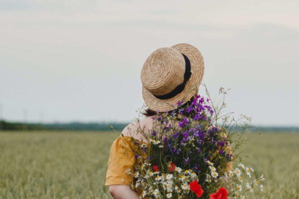 Kobieta stojąca tyłem w polu z kwiatami w rękach.