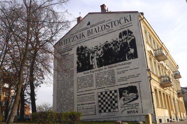 Budynek pokazany stroną szczytową z czarno-białym muralem.